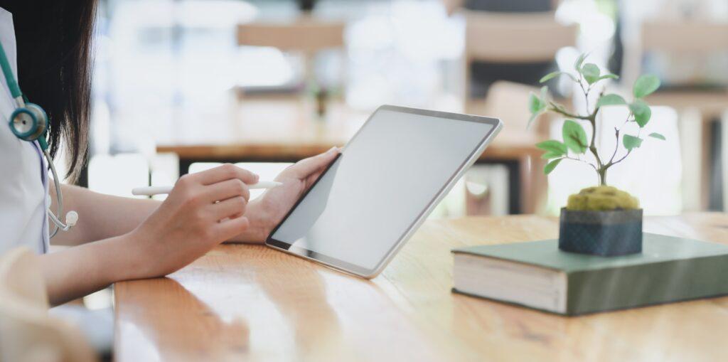 person-leaning-on-wooden-table-holding-white-tablet-3758759-1024x509 Segurança Social: conheça o acordo internacional entre Portugal e Brasil